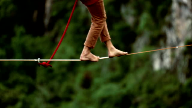 man traverses highline stretched above waterfall, valley - risk stock videos & royalty-free footage