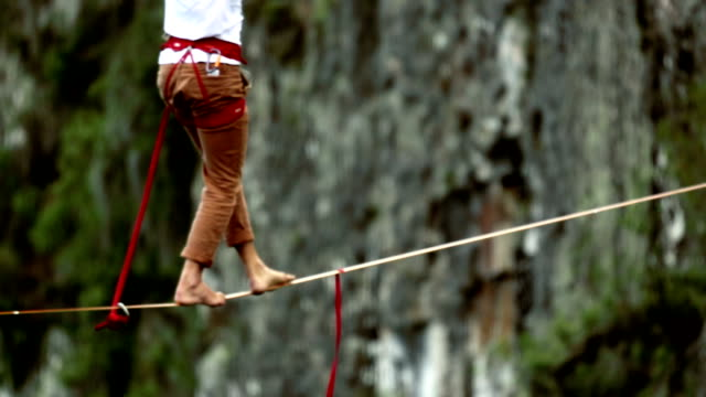 Man traverses highline stretched above waterfall, valley