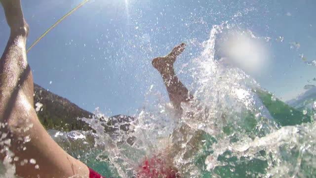 Man traverses slackline, falls into lake below
