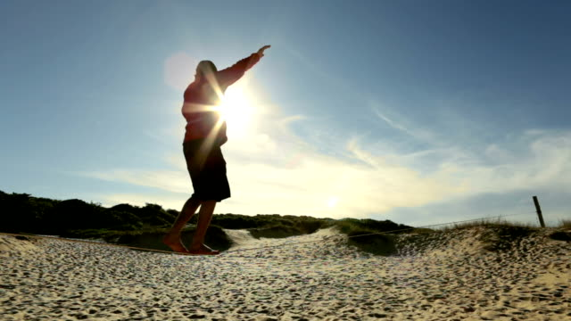 Man traverses slackline stretched above sandy dune area