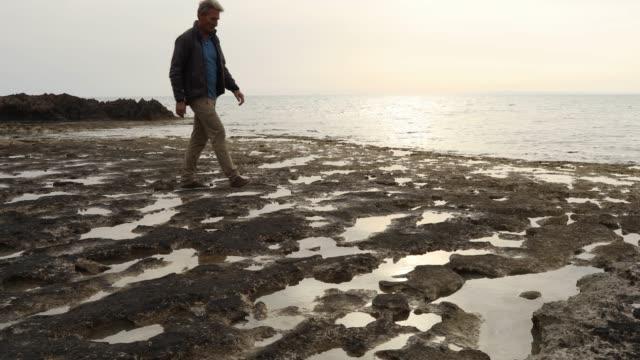 man traverses tidal pools along coastal flat - tide pool stock videos & royalty-free footage