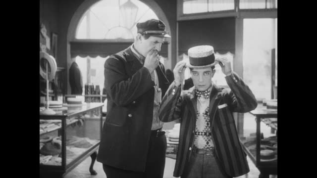 1928 Man (Buster Keaton) tries on many hats only to loose hat to gust of wind
