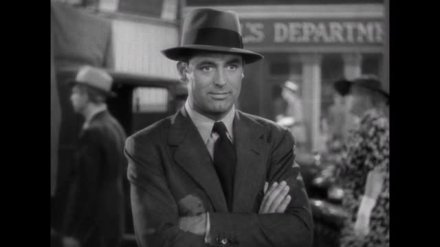 1941 man (cary grant), tries to attract woman's (irene dunne) attention while enthusiastic record shop clerk gets in the way - ミュージックショップ点の映像素材/bロール