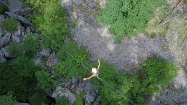 vidéos et rushes de a man tries to balance while slacklining on a tightrope. - corde