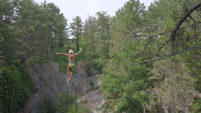 A man tries to balance while slacklining on a tightrope.