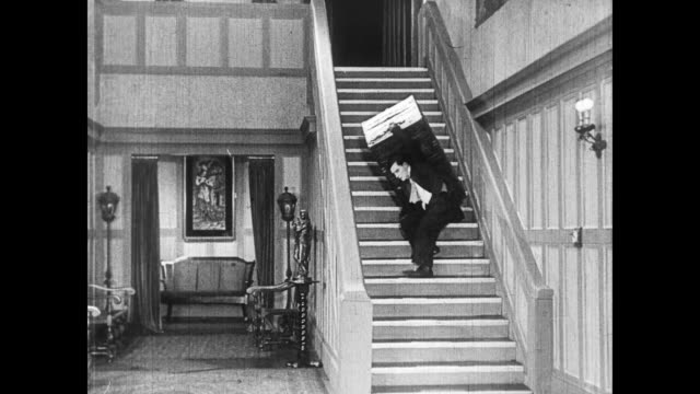 1922 man (buster keaton) tries to carry heavy trunk up electrified staircase - carrying stock-videos und b-roll-filmmaterial