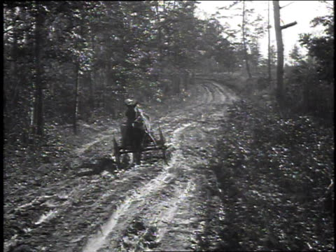 1925 WS Man tries to drive carriage down muddy road but encounters difficulty / United States