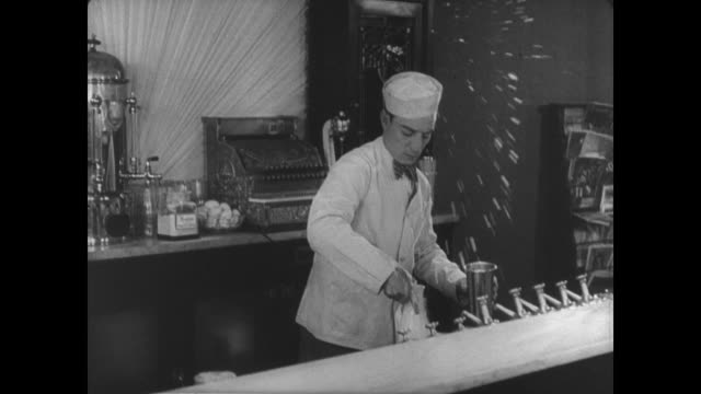 1927 Man (Buster Keaton) tries to emulate his coworker's theatrical soda fountain technique with less than desirable results
