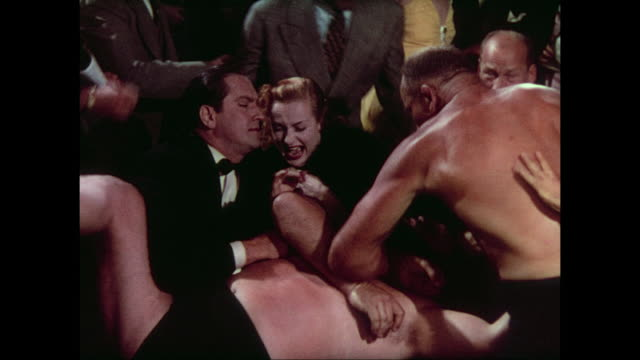 1937 man (fredric march) tries to help a screaming woman (carole lombard) who is surprised by wrestlers falling from ring into her lap - careless stock videos & royalty-free footage