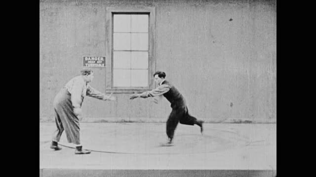vidéos et rushes de 1920 man (fatty arbuckle) tries to help another man (buster keaton) off of the spinning turntable - rouler ou dérouler