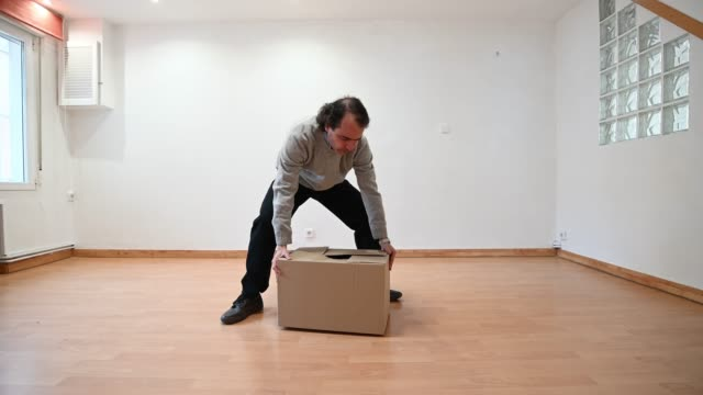 man tries to lift very heavy cardboard box in an empty and unfurnished room. move - picking up stock videos & royalty-free footage