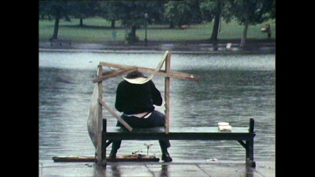 man tries to shield from rain under makeshift deckchair shelter; 1971 - vignette stock videos & royalty-free footage