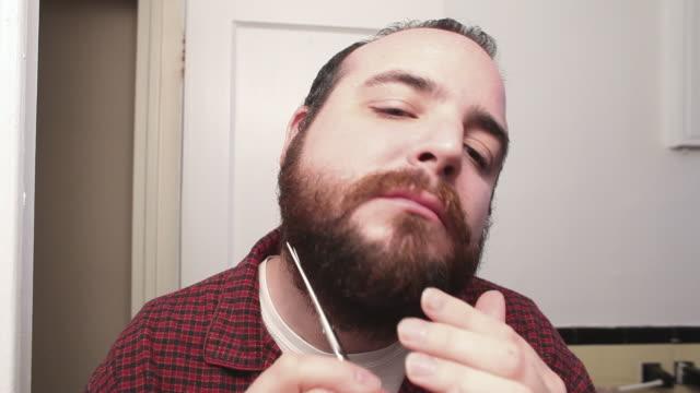 CU Man trimming beard with scissors / New York City, USA