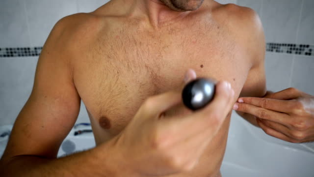 man trimming chest hair in bathroom - raso video stock e b–roll