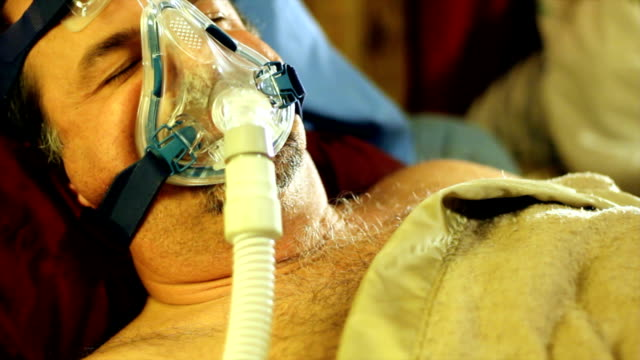 man tring to sleep with a cpap mask - snoring stock videos and b-roll footage