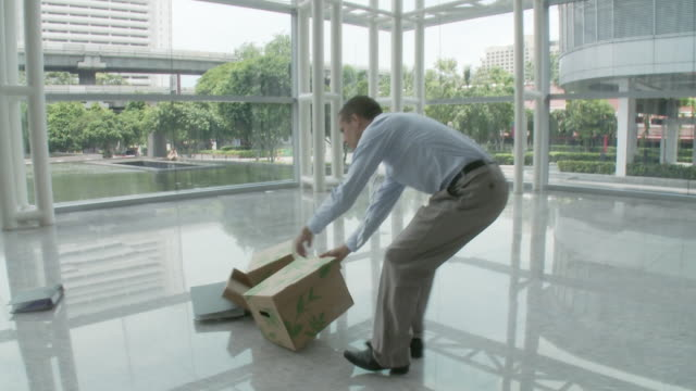ms pan man tripping and dropping cardboard boxes in lobby / bangkok, thailand - tripping falling stock videos and b-roll footage