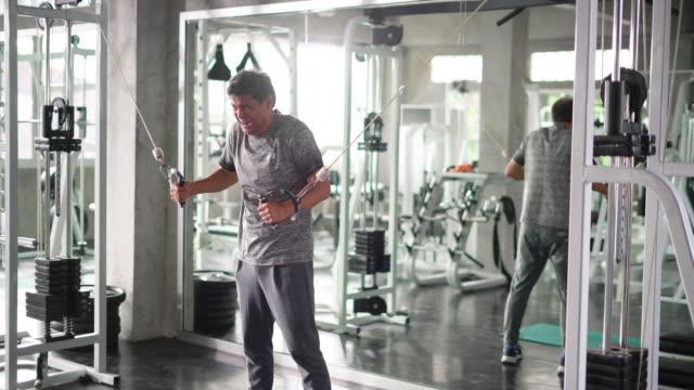 stockvideo's en b-roll-footage met man probeert moeilijk te trekken stretching kabel - tanden op elkaar klemmen