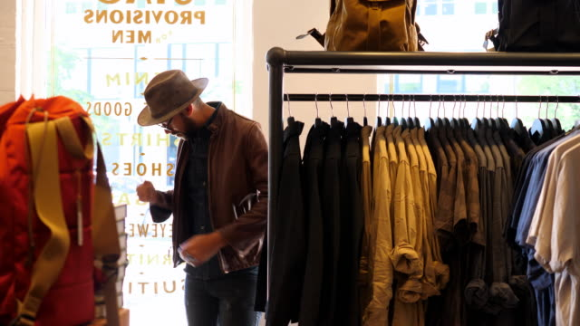 ms man trying on jacket in mens clothing shop - anpassen stock-videos und b-roll-filmmaterial