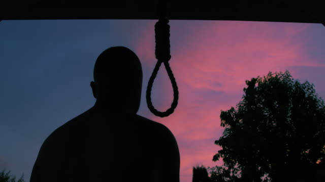 man trying to commit suicide by hanging himself on a hangman rope changing his mind and leaving in silhouette on a sunset sky background a concept new life - hinrichtung stock-videos und b-roll-filmmaterial