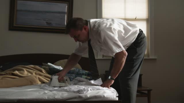 vídeos y material grabado en eventos de stock de man trying to iron clothing on a bed - plancha