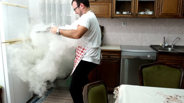 man trying to make dinner - burning video stock e b–roll
