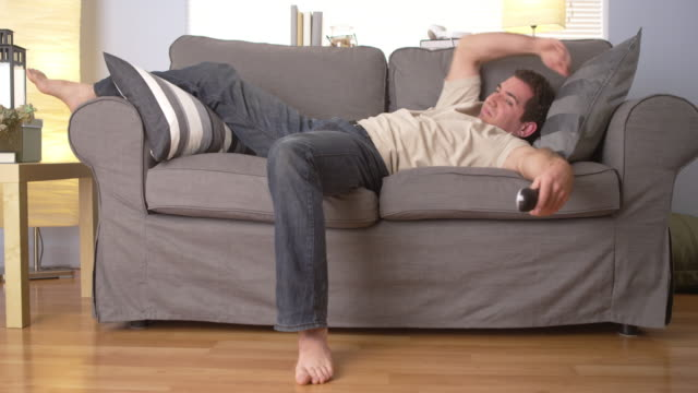 vídeos y material grabado en eventos de stock de man trying to sleep on couch - sofá