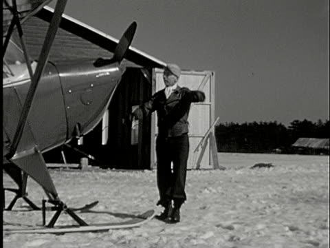 1935 ws man trying to spin airplane propeller to start engine on snow-covered airfield - propeller stock videos & royalty-free footage