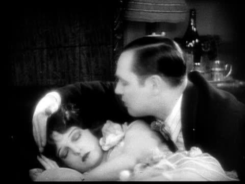 CU, B&W, Man trying to wake sleeping woman, 1920's