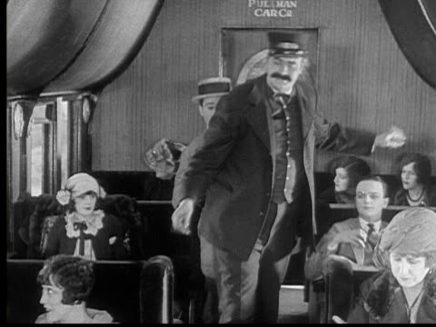 1924 b/w montage ms ws man (harry langdon) trying to walk past train conductor (tiny ward) in aisle / ms man jumping over seat and stepping on another man's hat / usa - train guard stock videos & royalty-free footage