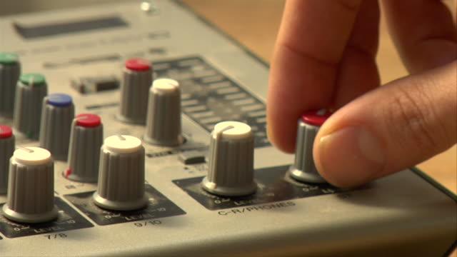 vídeos y material grabado en eventos de stock de cu, pan, man turning dial on sound mixer, close-up of hand - dial