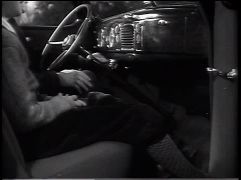 B/W 1937 man turning key in ignition of 1938 Ford V-8 sedan / boy sitting beside him / commercial