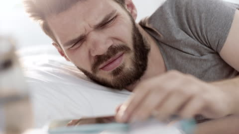 man turning off alarm on smartphone and keep sleeping - lying down stock videos & royalty-free footage