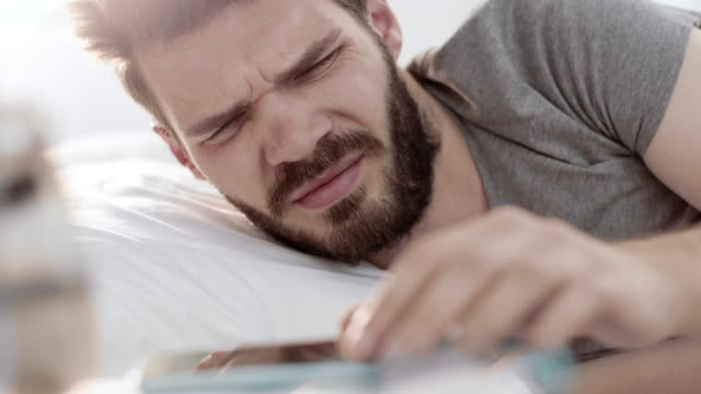 vídeos de stock e filmes b-roll de man turning off alarm on smartphone and keep sleeping - acordar