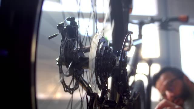 vidéos et rushes de slo mo ld man tournant les pédales tout en servant le vélo et la roue arrière tourne - rouage mécanisme