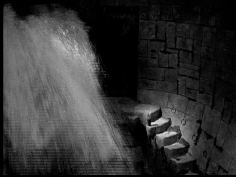 1925 cu ms b/w man turning valve, water falling into dungeon, terrified woman leaning against wall - menschliche gliedmaßen stock-videos und b-roll-filmmaterial