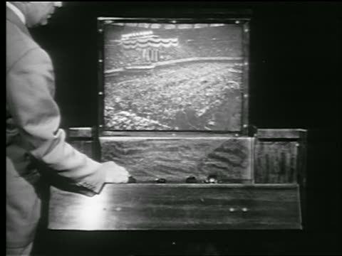 B/W 1948 man turns knob + watches political convention on television