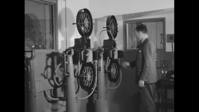 vidéos et rushes de man turns on large film projector in room and watches it operate / film reel on projector turning / note: exact year not known; documentation... - projecteur