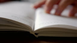 A man turns over the blank pages of the diary.