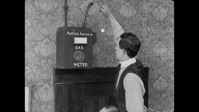 vídeos de stock e filmes b-roll de 1920 man (buster keaton) turns phonograph player into gas oven - gás estrutura física