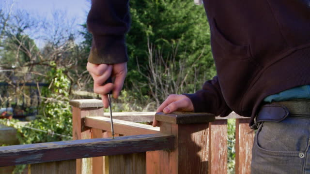 man turns screw into wooden rail - decking stock videos & royalty-free footage