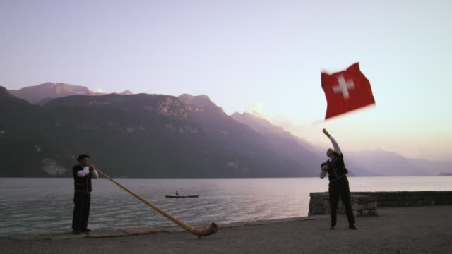 vídeos de stock e filmes b-roll de man twirls and tosses swiss flag while standing near alphorn player - switzerland