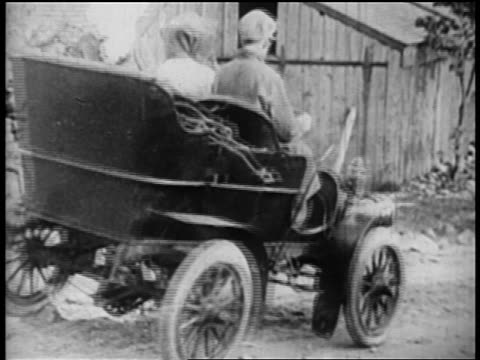 B/W 1905 man + two women driving in jiggling Ford car away from camera on dirt road / newsreel