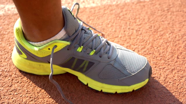 vídeos de stock, filmes e b-roll de homem amarrando os sapatos de exercício na pista de corrida - tênis calçados esportivos