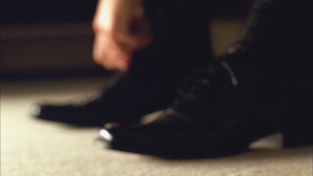 cu man tying pair of black dress shoes / new york - schuhwerk stock-videos und b-roll-filmmaterial