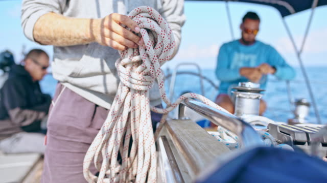 4k man tying rigging rope on sailboat, real time - crew stock videos & royalty-free footage