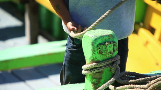 ms man tying rope to cleat on dock / valparaiso, valle central, chile - tie stock videos and b-roll footage