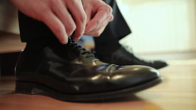 vídeos de stock e filmes b-roll de man tying shoe laces close-up - vestido