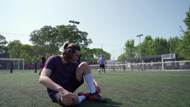 サッカーの試合前に靴ひもを結ぶ男 - ライバル点の映像素材/bロール