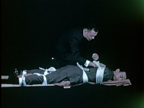 MS, Man tying unconscious man onto makeshift stretchers