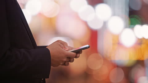 a man types on a mobile phone with lights in the background - part of a series stock videos & royalty-free footage